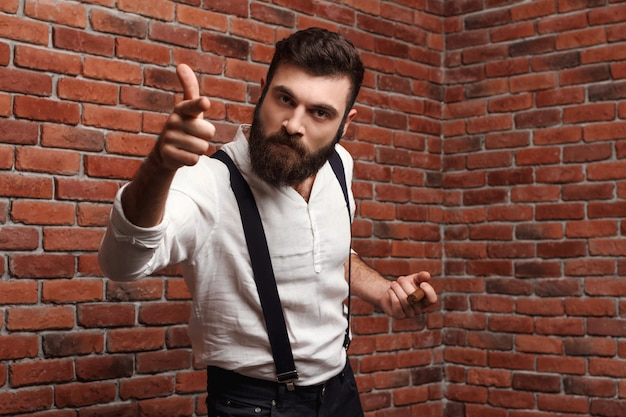 Rage brutale jeune bel homme fumant un cigare sur le mur de briques.