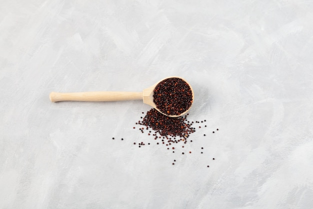 Ragi ou quinoa noir dans une cuillère en bois sur fond gris, espace de copie de mise au point sélective