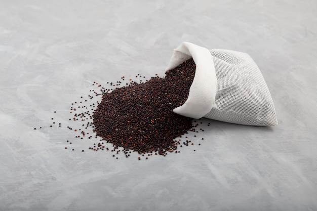 Ragi ou quinoa noir dans une pochette sur fond gris, espace de copie de mise au point sélective
