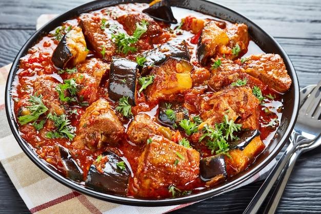 Ragoût de boeuf aubergine saupoudré de persil finement haché dans un bol sur une table en bois noir avec cuillère et fourchette en argent, vue horizontale d'en haut, gros plan