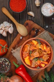 Ragoût de boeuf aux pommes de terre, carottes, perruque et épices (goulache hongroise) dans un bol en argile, vue du dessus