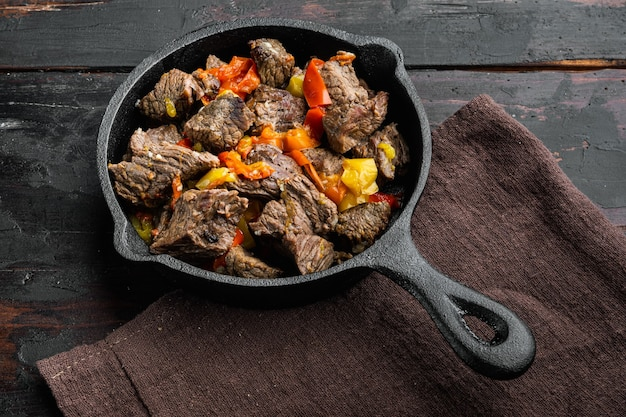 Ragoût de boeuf bourguignon aux légumes, dans une poêle en fonte, sur la vieille table en bois sombre