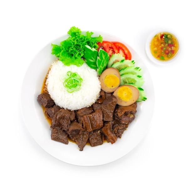 Ragoût de boeuf braisé avec recette de riz et d'oeufs servi poisson chili décoration de sauce découpage de légumes vue de dessus de style thaï