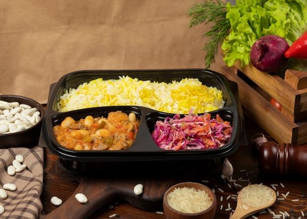 Ragoût de boeuf avec pommes de terre et marrons à la sauce tomate avec garniture de riz et salade de carottes au chou à emporter