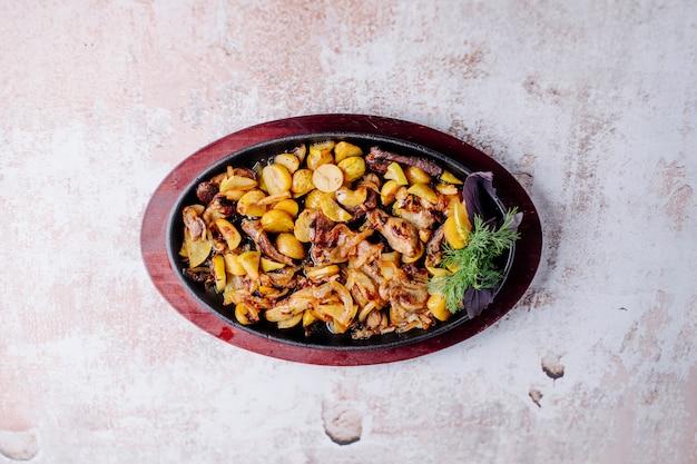 Ragoût de champignons avec des haricots et des châtaignes avec un bouquet d'aneth dans une casserole noire.