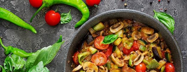 Ragoût chaud d'aubergine épicée, poivron, tomate, courgette et champignons. mise à plat. vue de dessus.