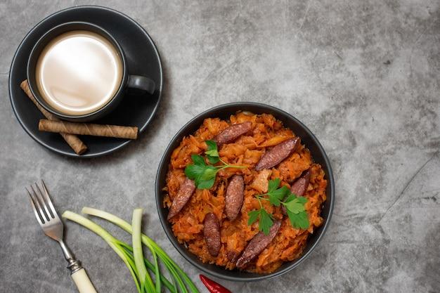 Ragoût de chou dans un bol avec des saucisses fumées et une tasse de café sur fond gris. vue de dessus,