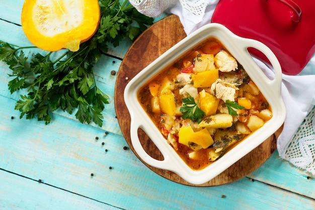 Ragoût de dinde aux légumes de citrouille et épices dans un bol sur une table en bois