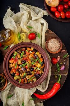 Ragoût épicé chaud (caponata) aubergine, courgette, poivron, tomate, carotte, oignon, olives et câpres. mise à plat. vue de dessus