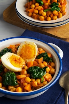 Ragoût espagnol de pois chiches et d'épinards avec des oeufs sur fond gris clair. cuisine espagnole.
