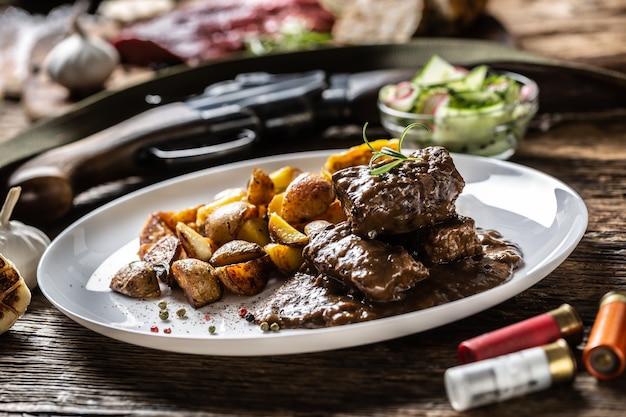 Ragoût de goulasch de gibier sauvage servi sur une assiette en porcelaine blanche avec pommes de terre rôties et assaisonné