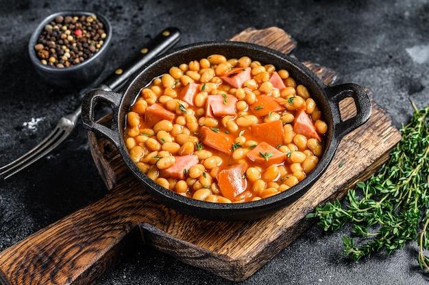 Ragoût de haricots rouges avec saucisse fumée et sauce tomate dans une casserole. fond noir. vue de dessus. copiez l'espace.