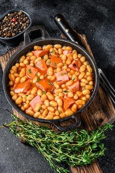 Ragoût de haricots rouges avec saucisse fumée et sauce tomate dans une casserole. vue de dessus.