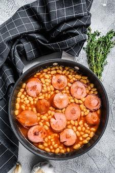 Ragoût de haricots avec saucisse fumée et sauce tomate dans une casserole. vue de dessus.