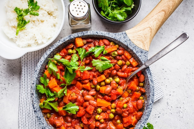 Ragoût de haricots végétaliens avec tomates et riz dans une casserole