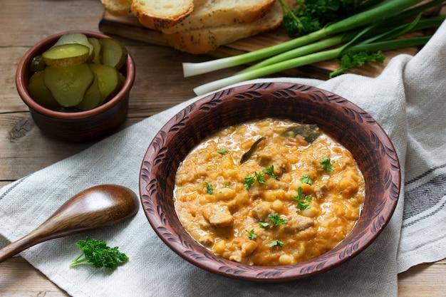 Ragoût de haricots et de viande, servi avec des cornichons, du pain et de l'ail. style rustique.