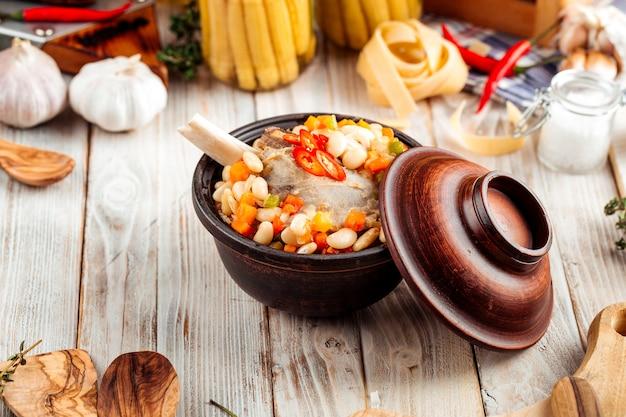 Ragoût de légumes aux haricots et os de bœuf en pot
