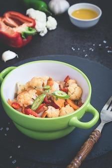 Ragoût de légumes de chou-fleur, carottes et poivrons sur fond noir