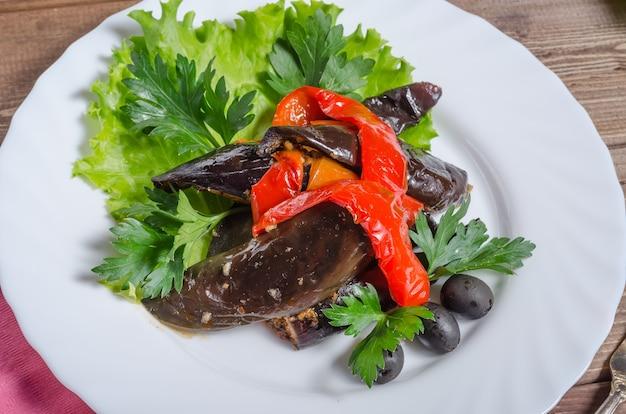 Ragoût de légumes de compote d'aubergines et de poivre dans un gros plan de plaque blanche