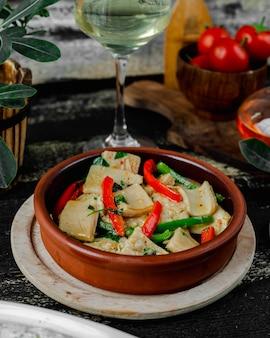 Ragoût de légumes à l'intérieur d'une assiette en poterie avec verre de vin blanc.