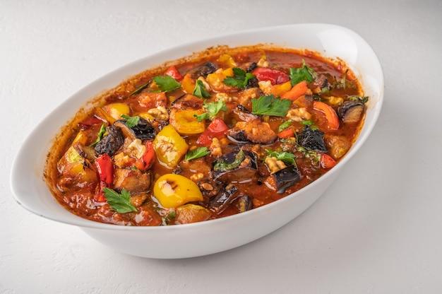 Ragoût de légumes maison d'aubergines, courgettes, tomates, ail, poivrons, pruneaux et verts sur bol sur table lumineuse.