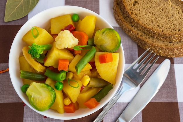 Ragoût de légumes (pommes de terre, asperges, carottes, choux de bruxelles, maïs, pois, chou frisé, brocoli) dans un bol blanc. vegan.