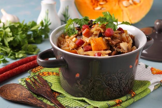 Ragoût de légumes avec des saucisses de chasse dans un pot en céramique sur fond bleu clair, gros plan