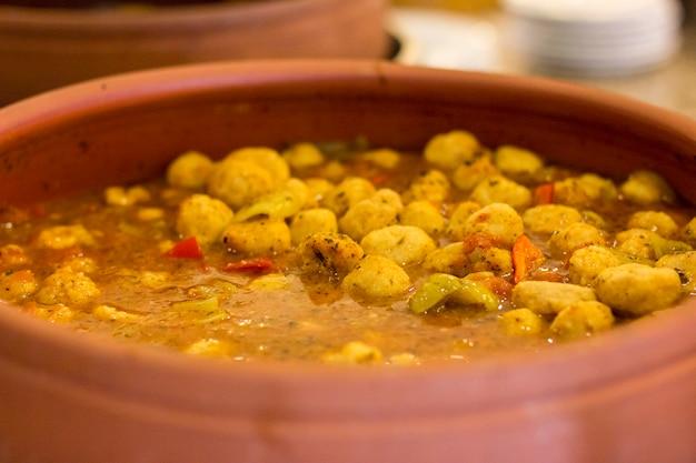 Ragoût de pommes de terre avec des légumes dans une grande casserole en argile