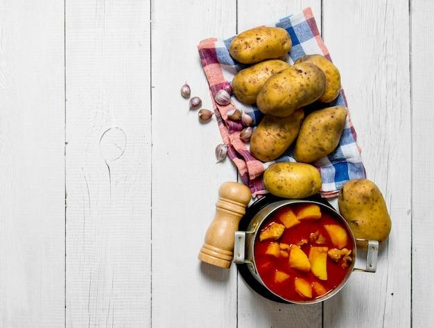Ragoût de pommes de terre avec de la viande et des épices sur fond de bois blanc