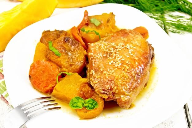 Ragoût de poulet à la citrouille, abricots secs, carottes et vin rouge, saupoudré de graines de sésame dans une assiette sur une serviette sur fond de planche de bois clair
