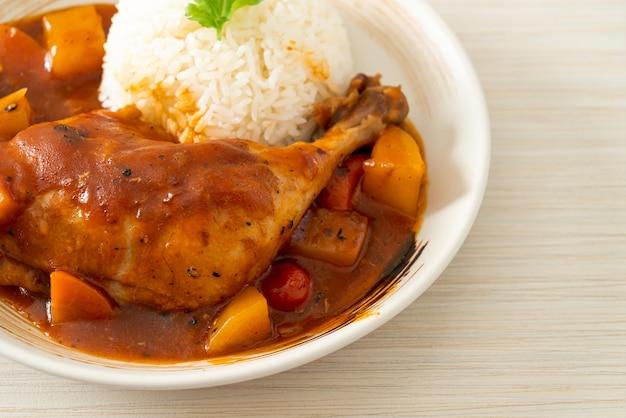 Ragoût de poulet maison avec tomates, oignons, carottes et pommes de terre sur assiette avec riz
