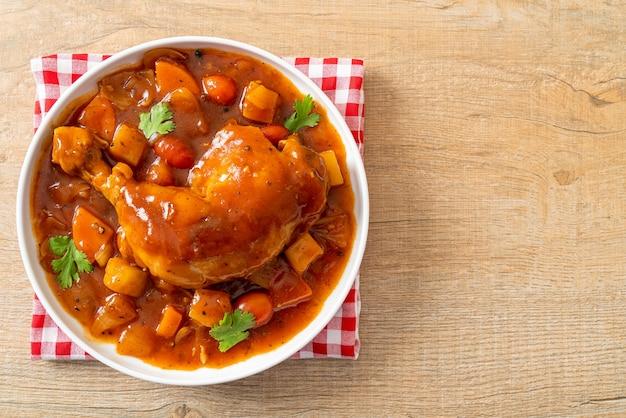 Ragoût de poulet maison avec tomates, oignons, carottes et pommes de terre sur assiette