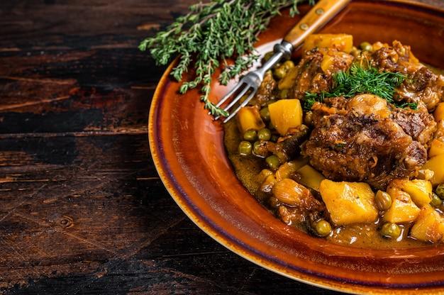 Ragoût de queues de boeuf aux légumes dans une assiette rustique. fond en bois foncé. vue de dessus. copiez l'espace.