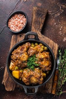 Ragoût de queues de boeuf avec du vin et des légumes dans une casserole. fond sombre. vue de dessus.