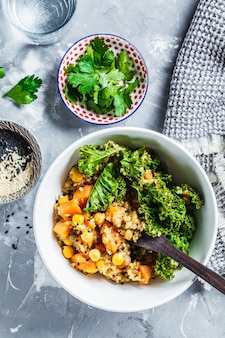 Ragoût végétalien avec pois chiches, patate douce et chou frisé dans un bol blanc, vue de dessus.
