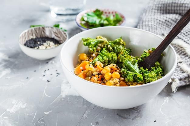Ragoût végétalien avec pois chiches, patates douces et chou frisé dans un bol blanc.