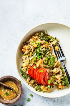 Ragoût végétalien avec pois chiches, patates douces et tomates fraîches sur une plaque blanche.