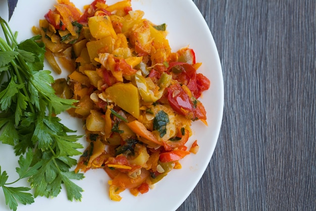 Ragoût végétarien de légumes d'été (courgettes, carottes, tomates, épices, ail, piment) dans un bol blanc sur un fond en bois. plat diététique.