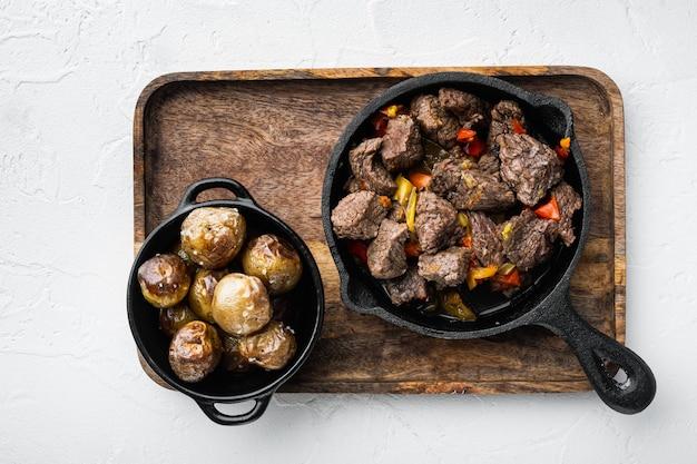 Ragoût de viande de boeuf et de légumes servi, dans une poêle en fonte, sur une surface en pierre blanche, vue de dessus à plat