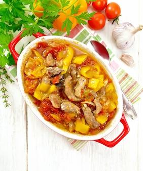 Ragoût de viande de dinde, tomate, poivron jaune et oignon avec sauce dans un brasero sur une serviette contre une planche de bois clair sur le dessus