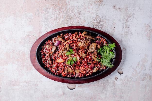 Ragoût de viande avec des épices et des herbes à l'intérieur de casserole noire.