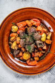 Ragoût de viande, goulasch sur une assiette. fond blanc. vue de dessus.