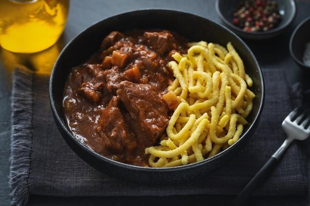 Ragoût de viande avec nouilles servi dans un bol sur fond sombre. fermer.