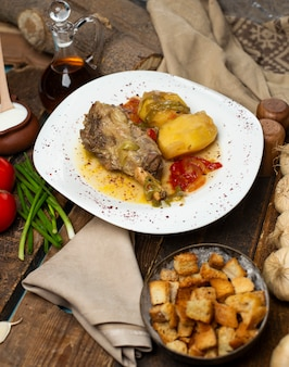 Ragoût de viande avec pommes de terre et bouillon huileux dans une assiette blanche avec biscottes.