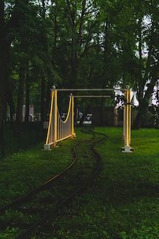 Rails et arche du chemin de fer à voie étroite dans le parc d'attractions du soir