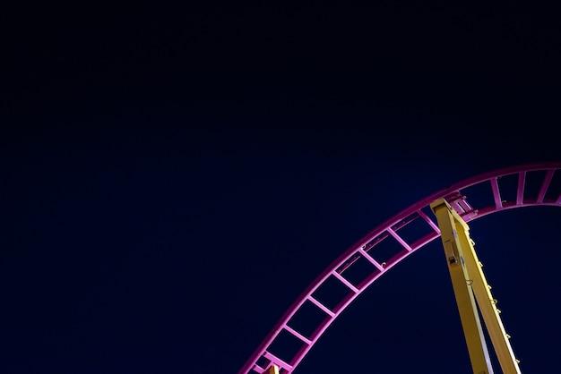 Rails d'un montagnes russes, fond de ciel bleu nuit.