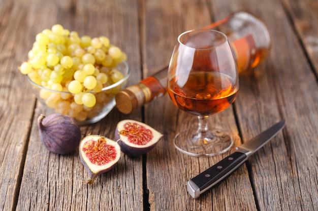 Raisin, figues et miel avec un verre de vin blanc sur fond de bois