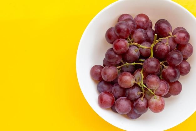 Raisin frais dans un bol blanc sur fond jaune.