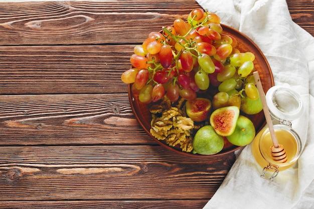 Raisin, fromage, figues et miel avec du vin sur une table en bois