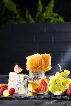 Raisin, fromage, figues et miel sur un fond noir de pierre